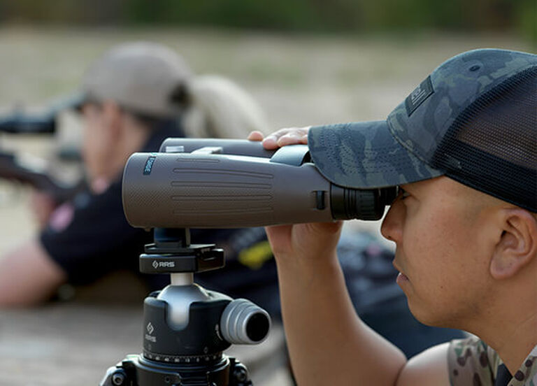 Competition shooter looking through Forge 15x56 Binoculars