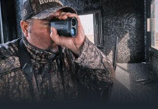 Hunter in deer blind looking through Bushnell Prime Laser Rangefinder