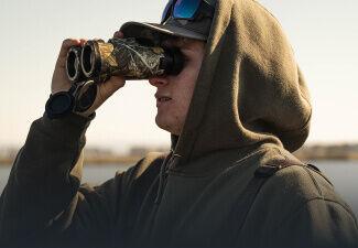 Hunter looking through Bushnell Engage X 10x42 Binoculars
