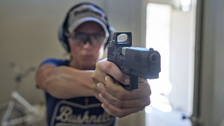 Woman holding a pistol with the Bushnell RXS-250 Reflex Sight