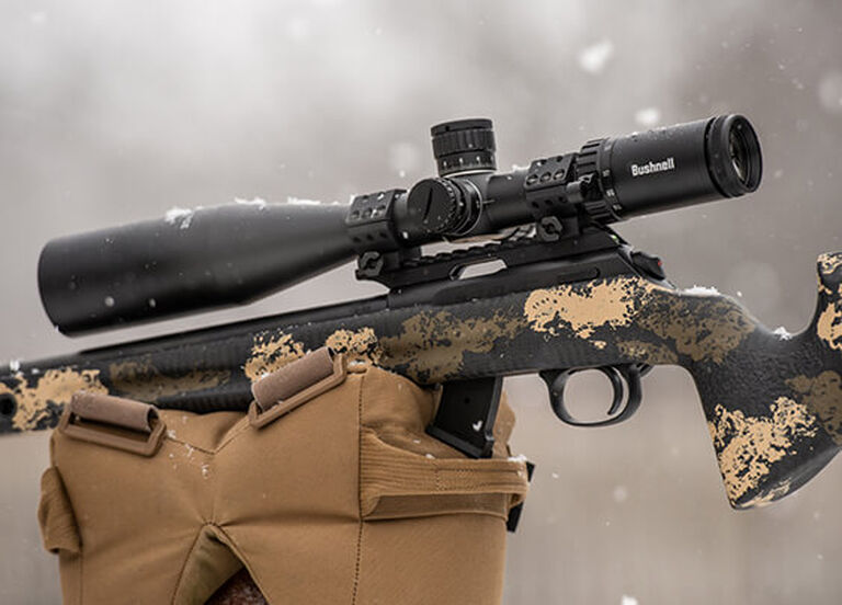 Bushnell Riflescope mounted on rifle, with a snowy background