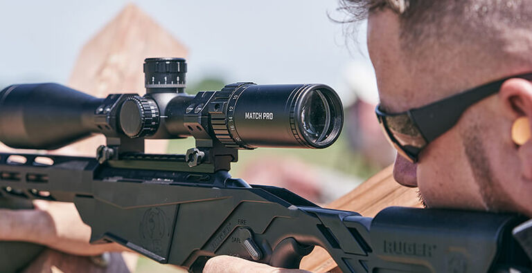 Competition shooter aiming with a Match Pro Riflescope mounted on rifle