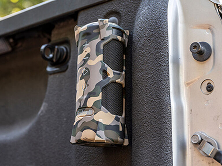Outdoorsman Bluetooth Speaker attached to a truck bed with BITE Magnetic Mount