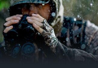 Hunter in the rain holding Bushnell Binoculars