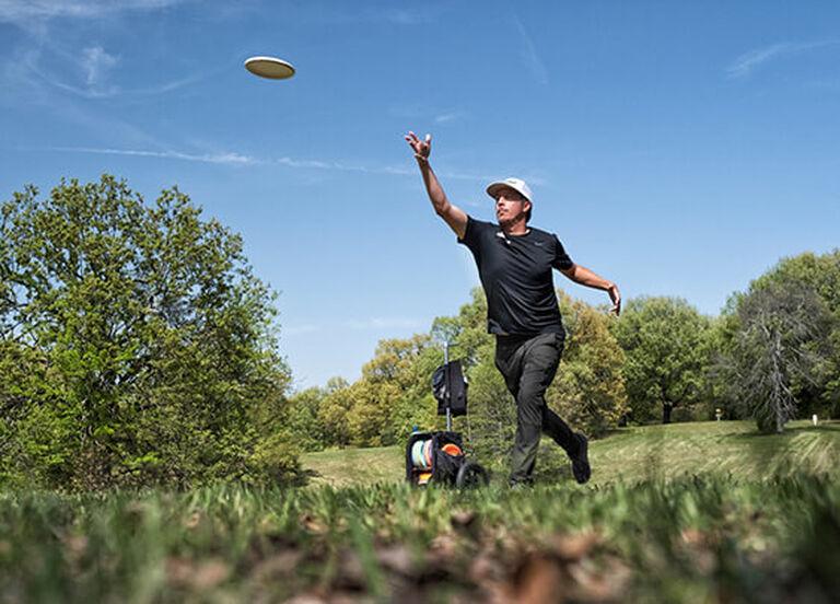 Man launching a disc golf drive