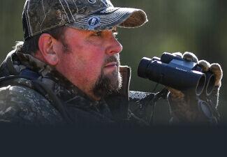 Hunter holding Bushnell Prime 10x42 Binoculars
