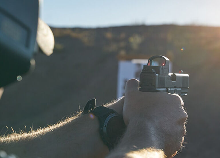 Man aiming pistol with Bushnell RSX Reflex Sight