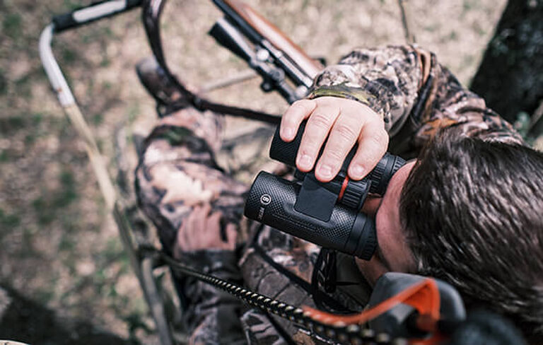 Hunter in tree stand looking through Nitro Binoculars