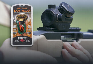 Shooter aiming through Trophy TRS-25 Red Dot mounted on shotgun