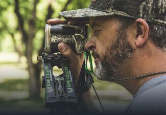 Hunter in deer blind looking through Bone Collector 850 LRF Realtree Edge