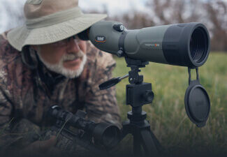 Man looking through Trophy Xtreme Spotting Scope mounted tripod