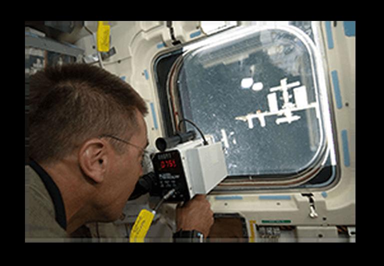 NASA astronaut using a laser rangefinder